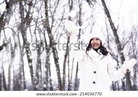 Pretty woman throwing a snowball enjoying winter time - stock photo