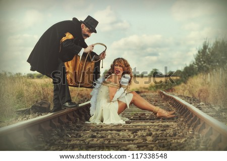 Pretty woman tied up on railway line by classic villain - stock photo