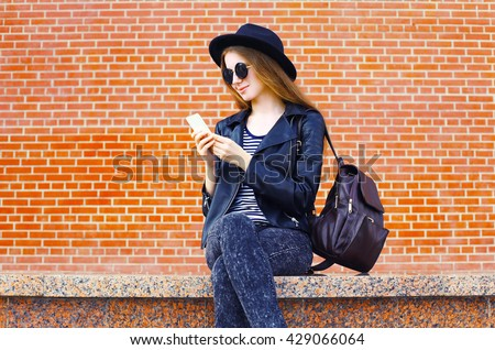 Pretty woman using smartphone in rock black style over bricks textured background - stock photo
