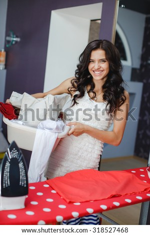 Pretty woman washing clothes in washer at home.woman doing a housework holding laundry. Happy young woman is doing laundry with washing machine at home. - stock photo