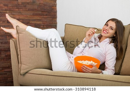 Pretty woman watching movie and eating pop corn - stock photo