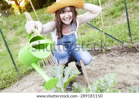 pretty woman watering plants in the garden - stock photo