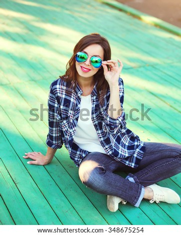 Pretty woman wearing a sunglasses and checkered shirt sitting in city - stock photo