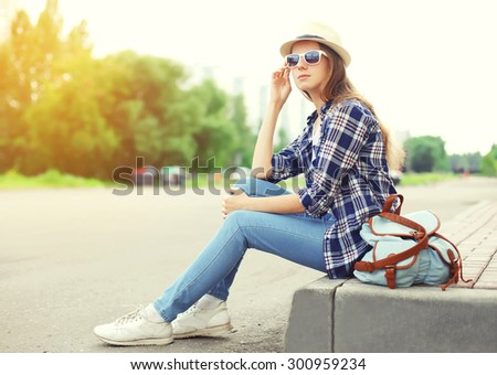 Pretty woman wearing a sunglasses, straw hat and backpack sitting outdoors in the city summer - stock photo