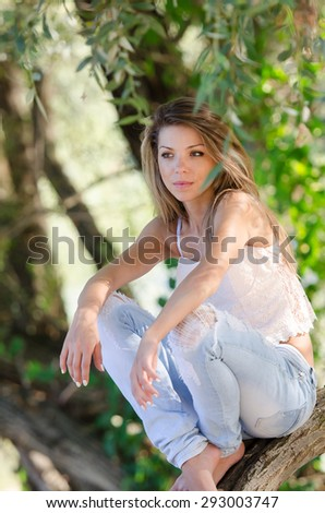 Pretty woman wearing blue jean sitting on a tree trunk in the beautiful scenery of river