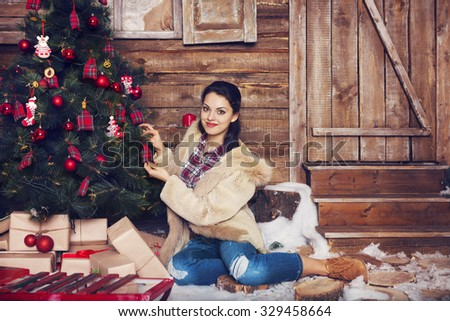 Pretty woman wearing fur coat sitting near the Christmas tree in wooden celebration Christmas interior  - stock photo