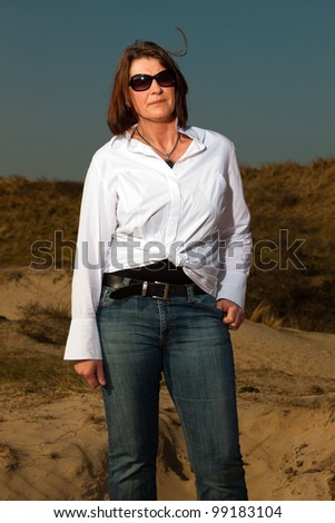 Pretty woman wearing sunglasses middle aged enjoying outdoors. Clear sunny spring day with blue sky. - stock photo