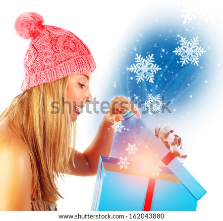 Pretty woman wearing warm hat opening great Christmas gift box and looking in it, isolated on white background, magical light and snowflakes - stock photo