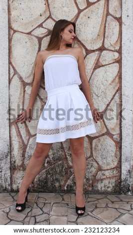 Pretty woman wearing white dress leaning on textured wall - stock photo
