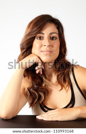 Pretty woman with a arm on a table and the other hand under her chin, and looking at the camera with a happy, friendly smile - stock photo