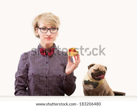 Pretty woman with a cake and her dog sitting by the table
