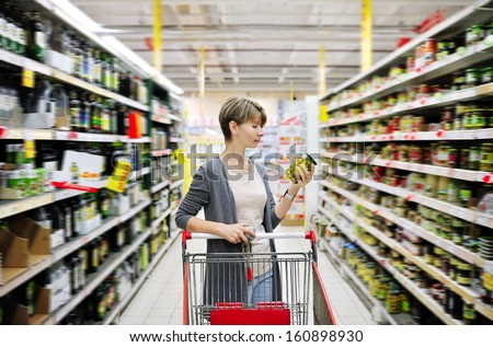 pretty woman with a cart shopping and choosing goods at the supermarket - stock photo