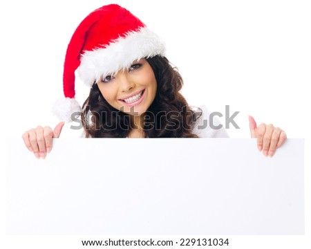 Pretty woman with a cute smile and long curly brown hair in a Santa hat displaying a blank white sign or placard with copyspace for your advertising or text - stock photo