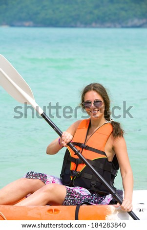 pretty woman with a paddle kayaking on the sea - stock photo