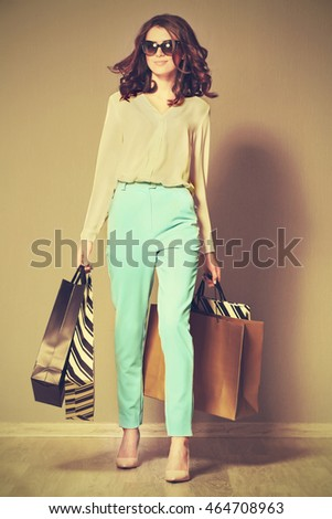 Pretty woman with bags on grey background