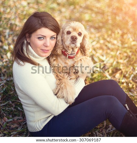 Pretty woman with beautiful cocker spaniel in autumn park
