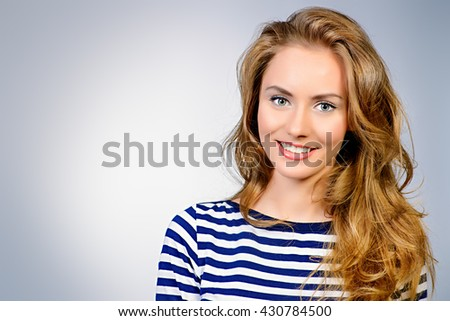 Pretty woman with beautiful long hair smiling at camera. Studio shot. - stock photo