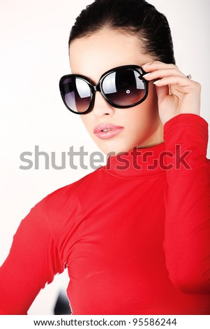 Pretty woman with big sun glasses red dressed - stock photo