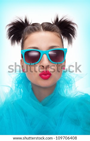 pretty woman with blue eyeglasses is blowing a kiss - stock photo