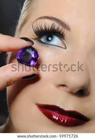 pretty woman with bright make-up and violet jewel stone - stock photo