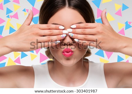 pretty woman with colorful gel nails hiding her eyes with fingers