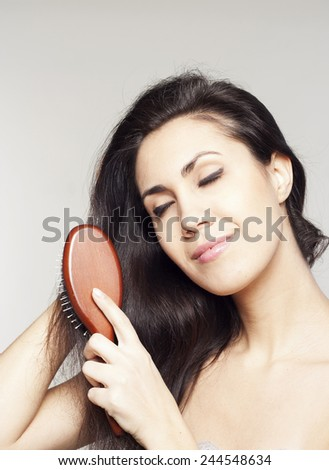 Pretty woman with comb in her hands - stock photo