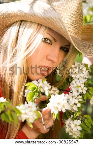 Pretty woman with cowboy hat and blossom trees