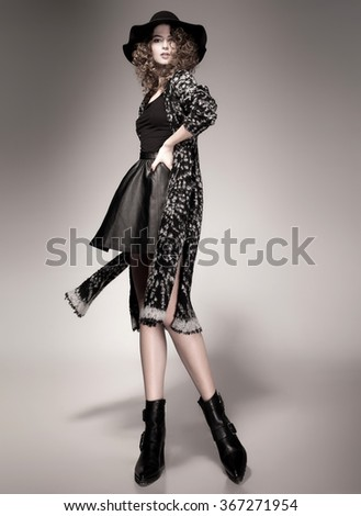 pretty woman with curly hair dressed casual posing in the studio