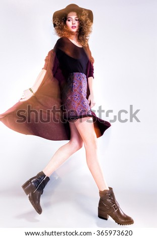 pretty woman with curly hair dressed casual posing in the studio - intentional motion light - stock photo