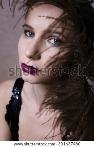 pretty woman with feather closeup fashion 1940-1980 make up - stock photo