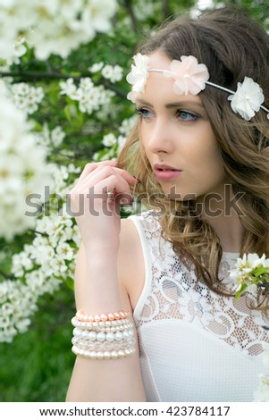 pretty woman with flower hair band in front of a blossoming apple tree / woman in nature