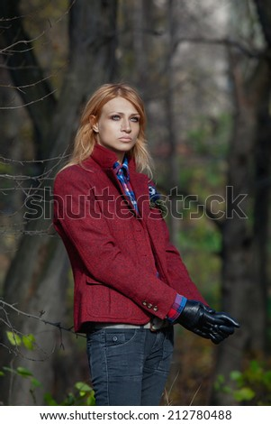 Pretty woman with flowing hair in tweed jacket and leather gloves walking in autumn forest - stock photo