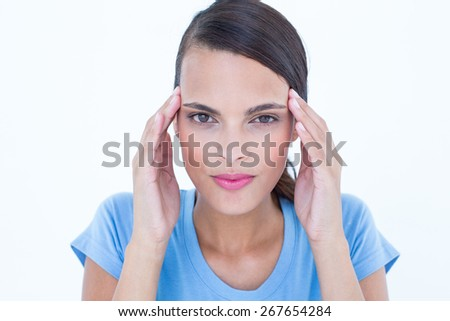 Pretty woman with headache touching her temples looking at camera on white background - stock photo