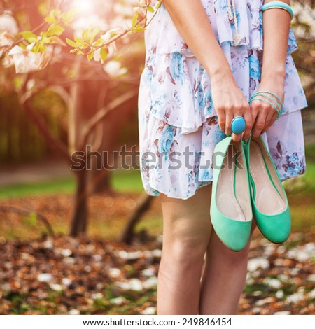 Pretty woman with her shoes in summer park - stock photo