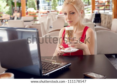 Pretty woman with laptop in cafe