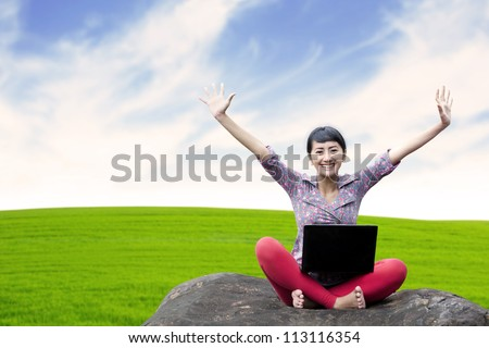 Pretty woman with laptop sitting on the stone under clear sky - stock photo