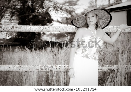 Pretty Woman with large hat in tall weeds and rusted fence. Photo in black and white. - stock photo