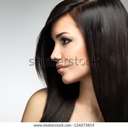 Pretty woman with long brown hairs.  Profile portrait of the fashion model posing at studio. - stock photo