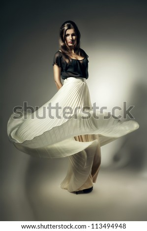 pretty woman with long flying skirt - stock photo