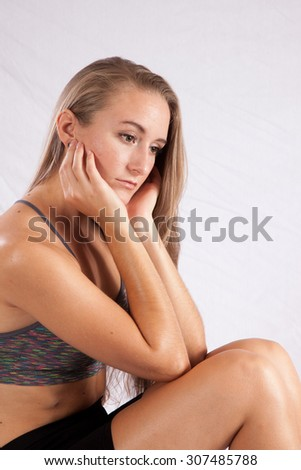 Pretty woman with long hair sitting thoughtfully