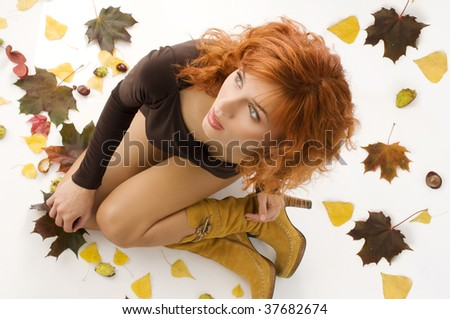 pretty woman with red hair in a shot from top with autumn leaves and chestnut around