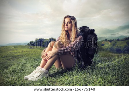pretty woman with rucksack sitting on the grass in the mountain
