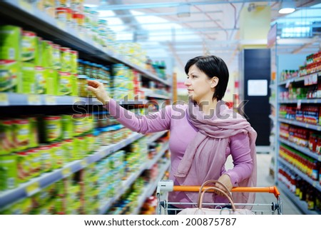 pretty woman with shopping cart choosing at goods in supermarket