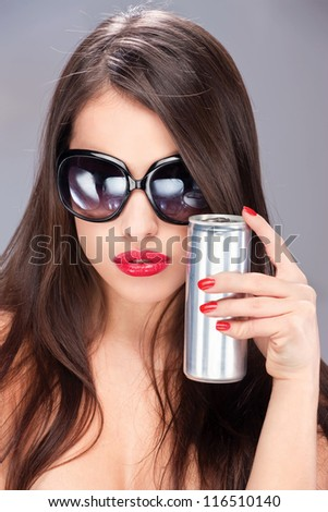 Pretty woman with sun glasses holding can - stock photo