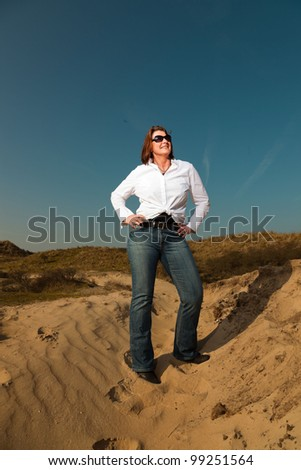 Pretty woman with sunglasses middle aged enjoying outdoors. Clear sunny spring day with blue sky. - stock photo