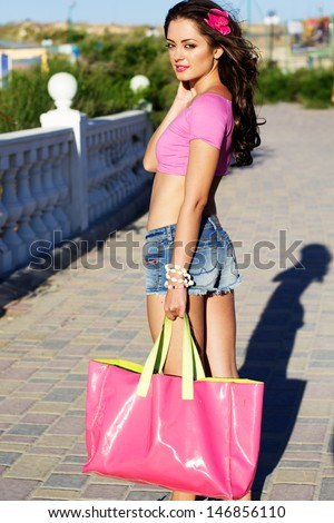 Pretty woman with the pink beach bag - stock photo