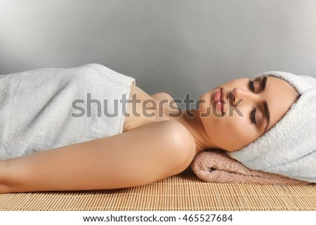 Pretty woman with towel on hair lying on table