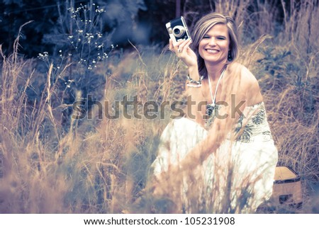 Pretty Woman with Vintage Camera sitting on suitcase in tall weeds. Photo in old color style. - stock photo