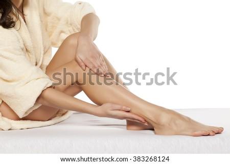 pretty women applied cream on her legs - stock photo