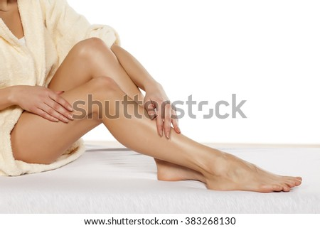 pretty women applied cream on her legs - stock photo